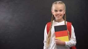Smiling female pupil holding German language textbook, blackboard background. Stock footage stock video footage
