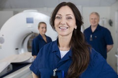 Smiling Female Radiologist With Colleagues Standing By MRI Machi Royalty Free Stock Photo