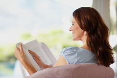 A smiling female reading book Stock Image