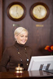 Smiling female receptionist at hotel counter Royalty Free Stock Images