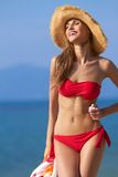 Smiling female in red bikini and straw hat Royalty Free Stock Image