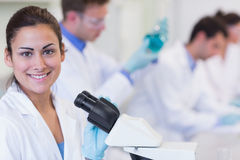 Smiling female with researchers working on experiments in lab Stock Photography