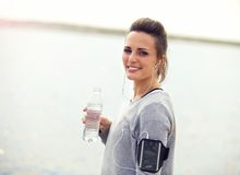 Smiling Female Runner Holding a Bottled Water Royalty Free Stock Image