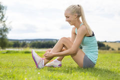 Smiling female runner tying shoe laces at the grass Stock Photography