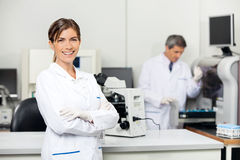 Smiling Female Scientist In Laboratory. Smiling mid adult female scientist with colleague working in background at medical laboratory Royalty Free Stock Image