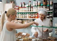 Smiling female seller and customer choosing nuts in shop. Portrait of smiling female seller and customer choosing nuts in shop royalty free stock images