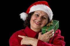 Smiling Female Senior with Red Santa Claus Cap. Happy elderly woman with a Santa Claus hat and a red coat. She is holding a green wrapped Christmas present to Royalty Free Stock Image