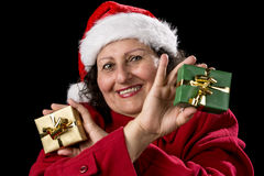 Smiling Female Senior Showing Two Wrapped Gifts. Gentle middle-aged woman with Father Christmas cap and red coat is cracking a smile. She is showing a green and Royalty Free Stock Photo