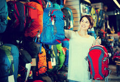 Smiling female shopper examining rucksacks in sports equipment s. Smiling female shopper examining аssortment of rucksacks in sports equipment store Stock Photography