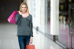 Smiling female in shopping mall walking with paper bags royalty free stock images