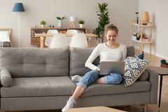Happy female relax on couch using laptop. Smiling female sit on cozy couch at home with laptop on knees browsing internet, happy girl spend weekend in apartment royalty free stock photo