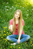 Smiling female sitting on the field of dandelions Stock Photos