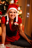 Smiling female sitting near Christmas tree Stock Image