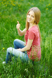 Smiling female sitting outdoors gesturing thumb up Royalty Free Stock Photos