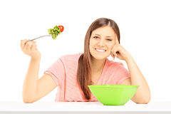 Smiling female sitting on a table and eating fresh salad Royalty Free Stock Images