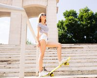 Smiling female skater in sunglasses looking up Stock Photos