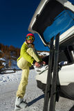 Smiling female skier putting her ski boots on. Full-length portrait of happy female skier putting her ski boots on, standing next to the car trunk Royalty Free Stock Image