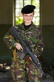 Smiling female soldier with a gun Stock Images