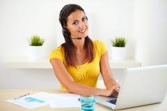 Smiling female speaking on her headphones stock photography