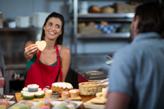 Smiling female staff giving heart shape cookie to customer at counter. In bake shop royalty free stock photo