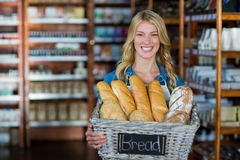 Smiling female staff holding a basket of breads Stock Photo