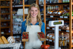 Smiling female staff holding box of cherry tomato in supermarket Stock Photo
