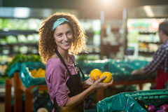 Smiling female staff holding fruits in organic section. Portrait of smiling female staff holding fruits in organic section of supermarket Stock Image