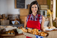 Smiling female staff holding wicker basket of various breads at counter Royalty Free Stock Image
