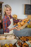 Smiling female staff holding wicker basket of various breads at counter Stock Photo