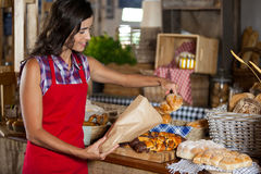 Smiling female staff packing sweet food in paper bag at counter Royalty Free Stock Photo