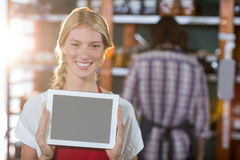 Smiling female staff showing digital tablet in supermarket. Portrait of smiling female staff showing digital tablet in supermarket Royalty Free Stock Photos