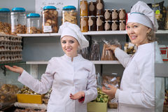 Smiling female staff in white robes offering sweets in local con. Friendly smiling female staff in white robes offering sweets in local confectionery stock photography