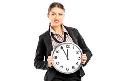 Smiling female standing and holding on a wall clock Royalty Free Stock Photo