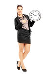Smiling female standing and pointing on a wall clock Stock Image