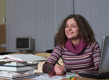 Smiling female student. Young female student is writing on papers. Nice smile royalty free stock photography