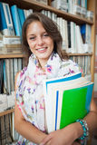 Smiling female student against bookshelf in the library Stock Photography