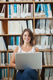Smiling female student against bookshelf using laptop in library Royalty Free Stock Image