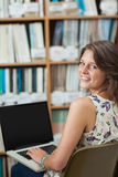 Smiling female student against bookshelf using laptop in library Stock Photography