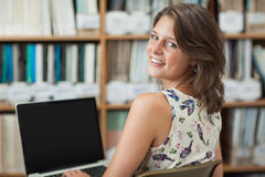 Smiling female student against bookshelf using laptop in library Royalty Free Stock Photography