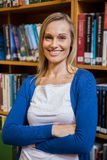 Smiling female student with arms crossed in the library Royalty Free Stock Image
