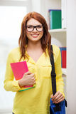 Smiling female student with bag and notebooks Royalty Free Stock Image