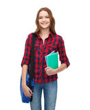 Smiling female student with bag and notebooks Stock Photos