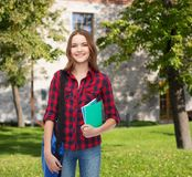 Smiling female student with bag and notebooks Stock Images