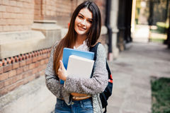 Smiling female student in black eyeglasses with folders and bag in the back stock image