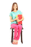 Smiling female student on a chair holding books Royalty Free Stock Photos