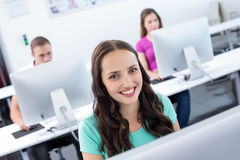 Smiling female student in computer class Stock Photography