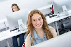 Smiling female student in computer class Stock Photos