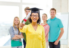 Smiling female student with diploma and corner-cap Royalty Free Stock Photos