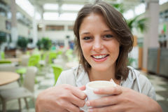 Smiling female student drinking coffee in the cafeteria Royalty Free Stock Photography