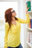Smiling female student in eyeglasses choosing book Stock Images